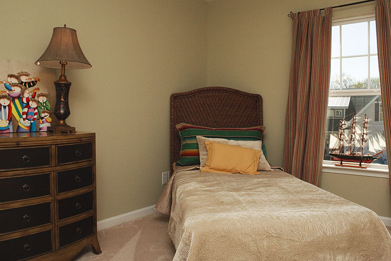 Photo of a single bed in the corner of a bedroom
