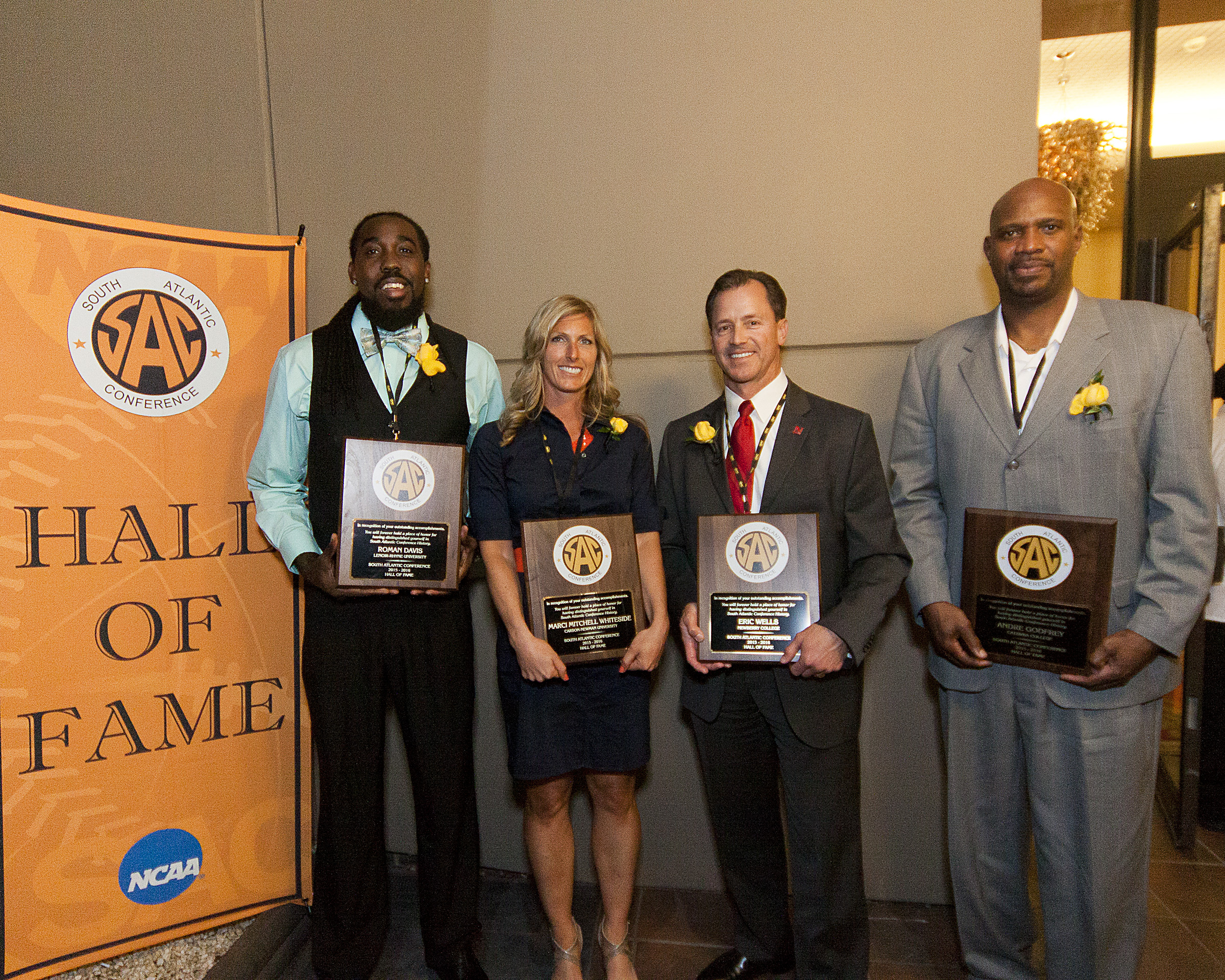 Four people being inducted into Hall of Fame stand next to a banner and hold their plaques