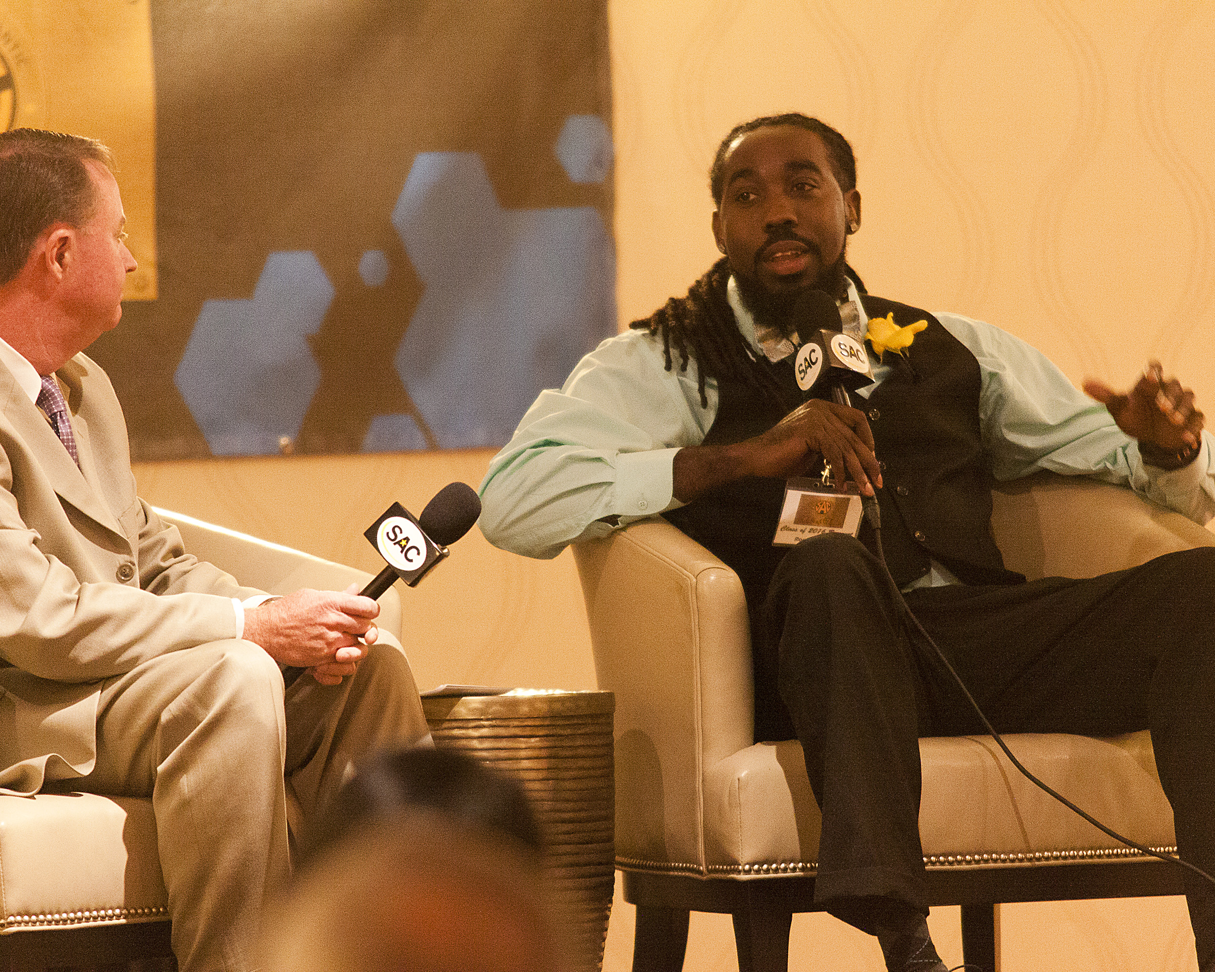 The emcee interviews one of the Hall of Fame inductees while they sit in chairs on a stage
