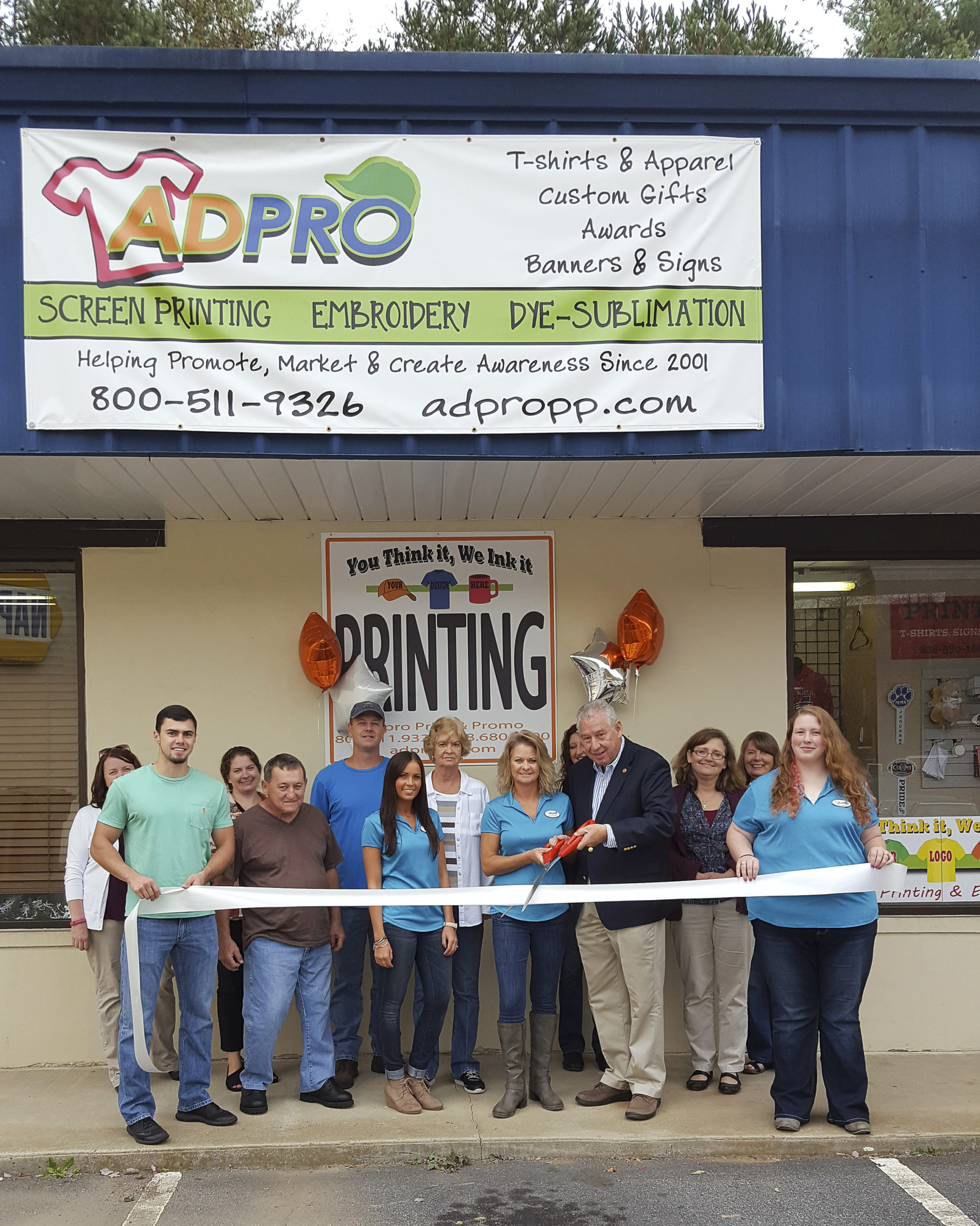 Photo of owner, family, employees, and chamber of commerce representative preparing to cut the ribbon for grant opening in front of Adpro store