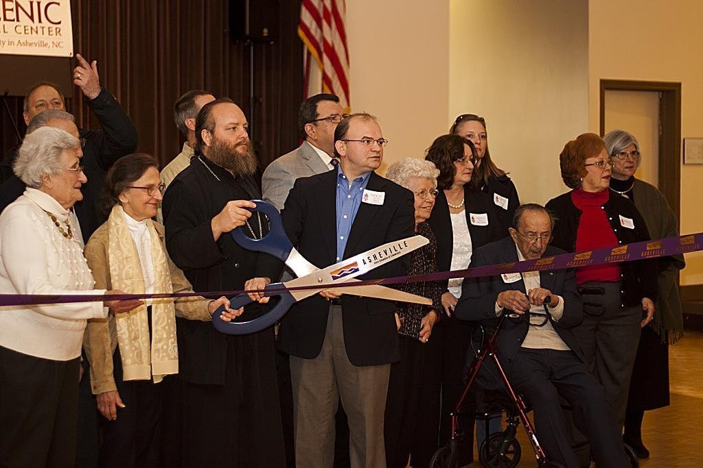 Photo of Hellenic Center staff/volunteers and chamber of commerce representative holding large scissors to cut ribbon