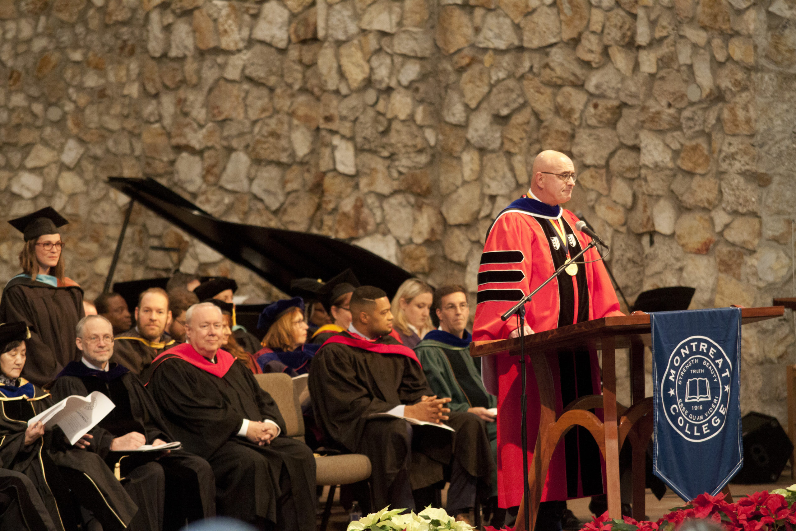 Photo of President Maurer standing at a podium with faculty seated behind him
