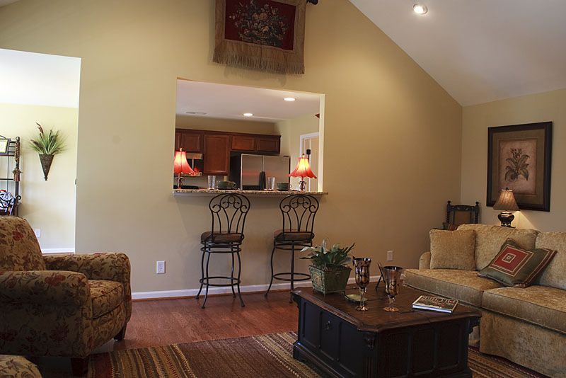 Photo of the living room with couch and coffee table, and stools at breakfast bar opening into kitchen