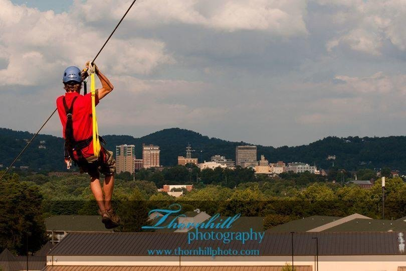 Photo of a man suspended from a zipline with the cityscape of downtown Asheville in the distance